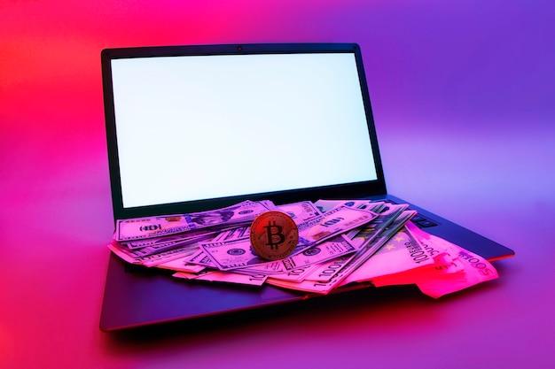 Makieta laptopa z białym ekranem i kryptowalutą bitcoin, dolary i euro na tle kolorowych jasnych neonowych niebieskich i fioletowych świateł uv.