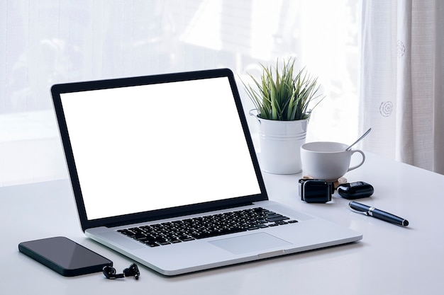 Makieta laptopa z ekranem balnk i gadżet na białym stole z jasnym jasnym tłem.