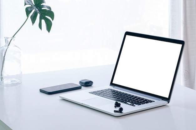 Makieta laptopa z ekranem balnk na białym stole z jasnym jasnym tłem.
