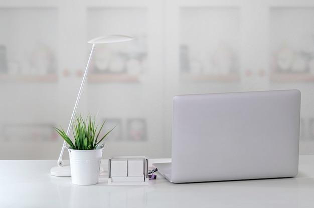 Makieta laptopa z lampą i rośliną doniczkową na białym blacie w nowoczesnym pokoju.