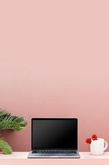 Makieta laptopa z pastelowo różową ścianą