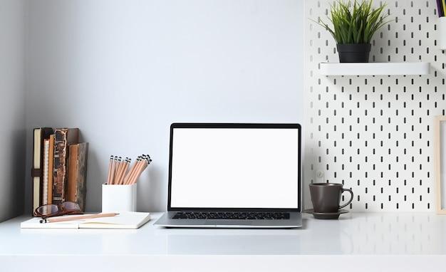 Makieta laptopa z pustym ekranem i materiały biurowe stawiają na białym biurku