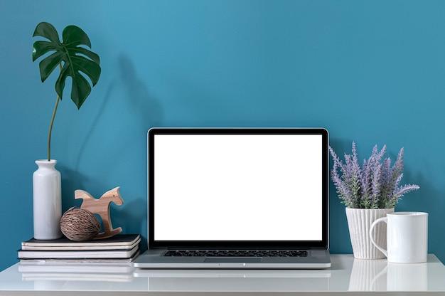 Makieta laptopa z pustym ekranem na białym blacie i jasnoniebieskiej ścianie.