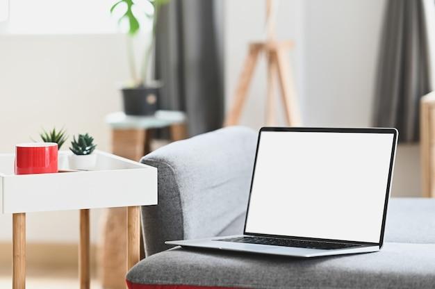Makieta laptopa z pustym ekranem na kanapie w salonie. do montażu wyświetlacza graficznego.