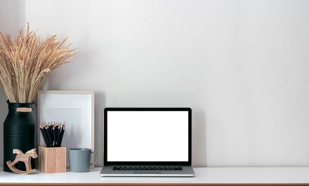 Makieta laptopa z pustym ekranem z drewnianym pudełkiem z ołówkiem, drewnianą ramą i rośliną doniczkową na białym blacie.