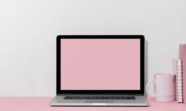 Makieta laptopa z pustym ekranem z kubkiem i książką na stole, kolor różowy.