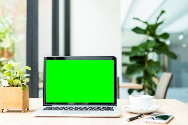Makieta laptopa z pustym zielony ekran z kawą