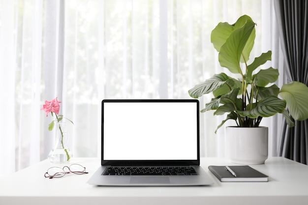 Makieta laptopa z różą i rośliną calathea orbifolia i notatnikiem na białym drewnianym stole