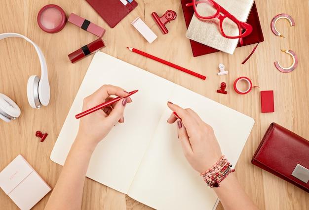 Makieta leworęczna kobieta pisze w pustym notatniku i czerwonym biurowym papeterii. widok płaski, widok z góry. planowanie dzienników, rysowanie. kreatywność, koncepcja biura domowego