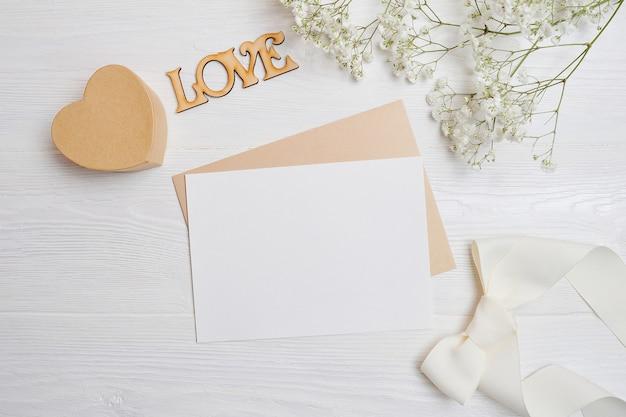 Makieta listu z pudełkiem miłosnym w kształcie serca leży na drewnianym białym stole z kwiatami łyszczec.