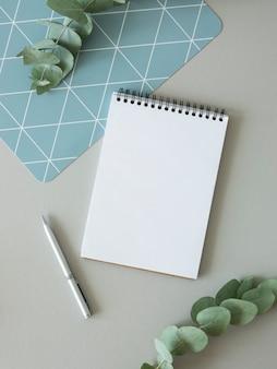 Makieta listy rzeczy do zrobienia. pusta strona notatnika z miejsca na kopię, pióro i gałąź eukaliptusa. widok z góry.