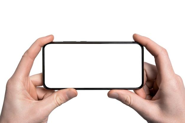Makieta, makieta. mężczyzna ręka trzyma czarny smartfon z ramką mniej pustego ekranu i nowoczesny design bez ramki, pionowy - na białym tle. ścieżka przycinania. interfejs projektowania ui.