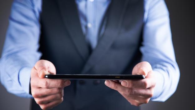 Makieta mężczyzny trzymającego w rękach cyfrowy tablet
