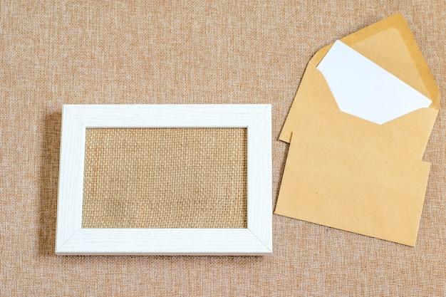 Makieta na biurko z białą drewnianą ramą na zdjęcia, kopertami na teksturowanej płótnie