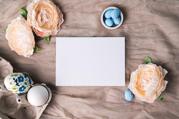 Makieta na gratulacje wielkanocne lub reklamy. szablon białej karty i pisanki z farbą akrylową