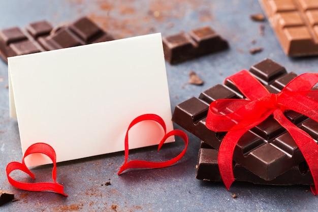 Makieta na walentynki. czekolada związana z czerwoną wstążką i pustą kartkę z życzeniami