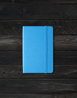Makieta niebieski notatnik zamknięty na białym tle na czarnym tle drewna