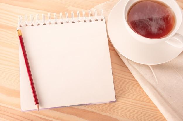 Makieta notatnik z pustą białą stroną z czerwonym długopisem na drewnianym stole i filiżanką gorącej herbaty