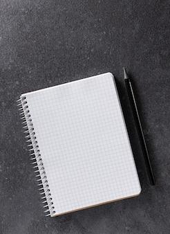 Makieta notebooka. papier a5 z czarnym ołówkiem na czarnym tle. widok z góry.