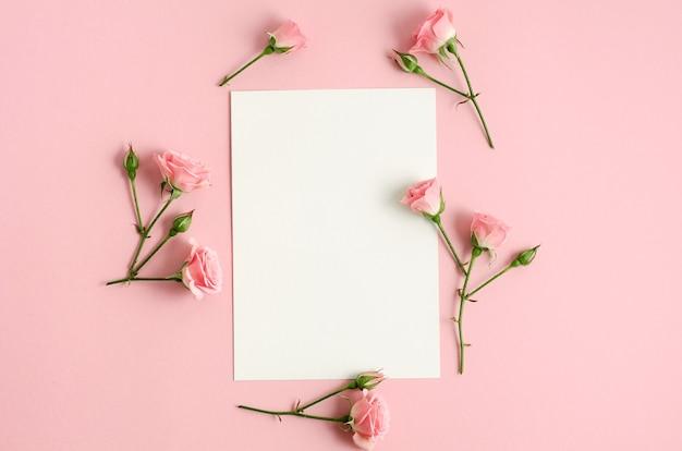 Makieta notesu i róż na różowym tle. zdjęcie z góry