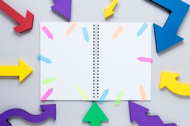 Makieta notesu płaskiego z kolorowymi strzałkami