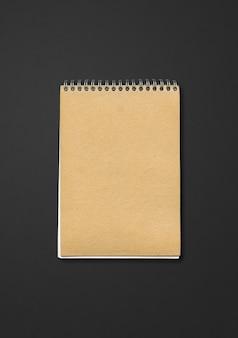 Makieta notesu zamknięta spirala, brązowa okładka papieru, na czarnym tle