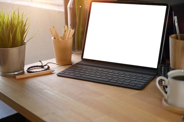 Makieta nowoczesna tabletka z klawiaturą na drewnianej przestrzeni roboczej i przestrzeni kopii.