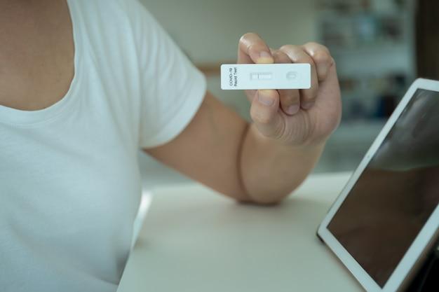 Makieta nowoczesny tablet z pustym ekranem na białym tle ze ścieżką przycinającą. młoda azjatka używa tabletu do prowadzenia rozmowy wideo online z lekarzem po pozytywnym wyniku testu na obecność antygenu covid-19.