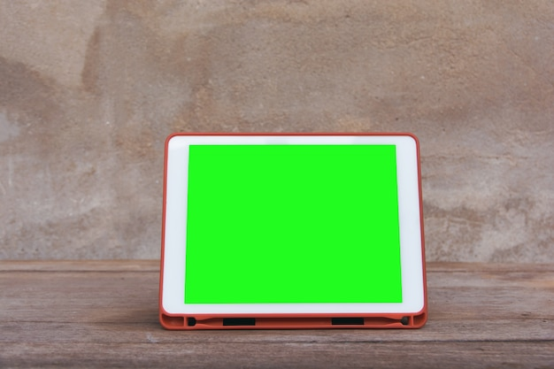 Makieta obraz biały tablet pc z pustym zielonym ekranie pulpitu na drewnianym stole