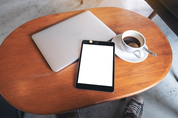 Makieta obraz czarny tablet pc z pustym pulpicie biały ekran z laptopem i filiżanką kawy na drewnianym stole
