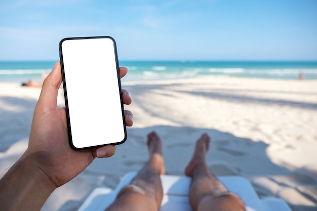 Makieta obraz dłoni mężczyzny trzymającego biały telefon komórkowy z pustym ekranem pulpitu, kładąc się na leżaku