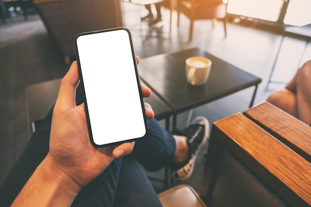Makieta obraz dłoni mężczyzny trzymającego czarny telefon komórkowy z pustym ekranem przy filiżance kawy na stole w kawiarni