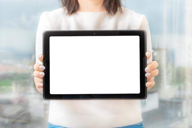 Makieta obraz kobiety gospodarstwa i pokazując czarny cyfrowy tablet z pustym ekranem.