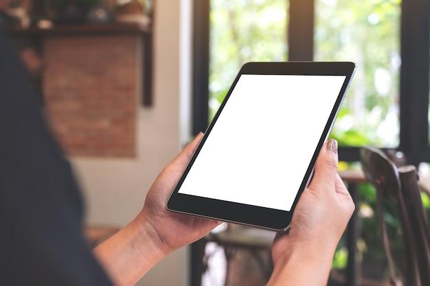 Makieta obraz kobiety ręce trzymając czarny tablet pc z pustym ekranem pulpitu w kawiarni