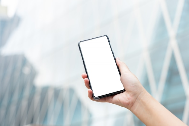 Makieta obraz kobiety ręki trzymającej smartfonów mobilnych na białym tle biały ekran