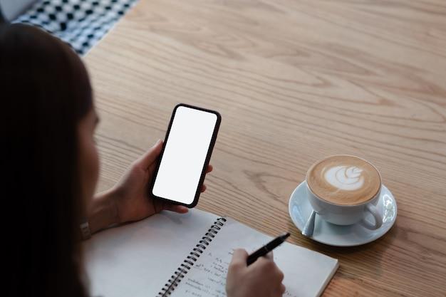 Makieta obraz kobiety trzymając telefon komórkowy z pustym czarnym ekranie w nowoczesnej kawiarni na poddaszu