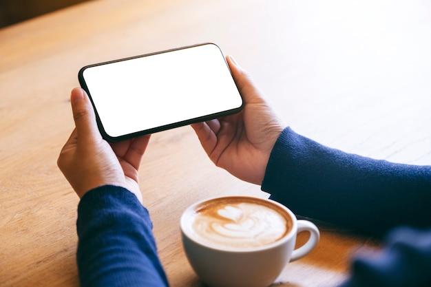 Makieta obraz kobiety trzymającej biały telefon komórkowy z pustym ekranem z filiżanką kawy na drewnianym stole
