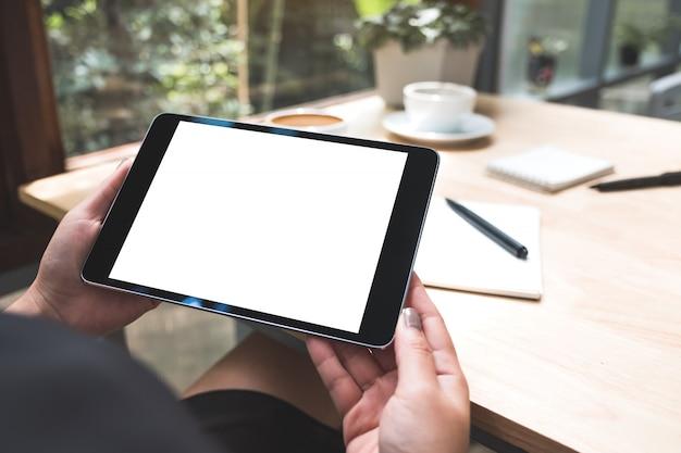 Makieta obraz kobiety w ręce trzyma czarny tablet pc z białym pustym ekranem z notebooka i filiżankę kawy na stole