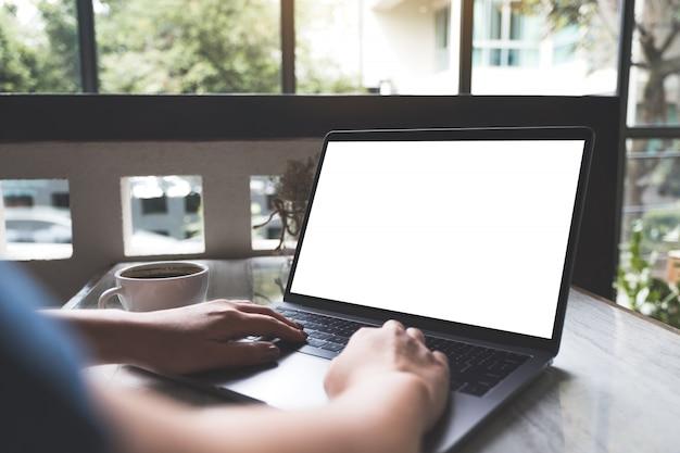 Makieta obraz kobiety za pomocą i pisania na laptopie z pustym białym ekranem i filiżankę kawy na stole w nowoczesnej kawiarni