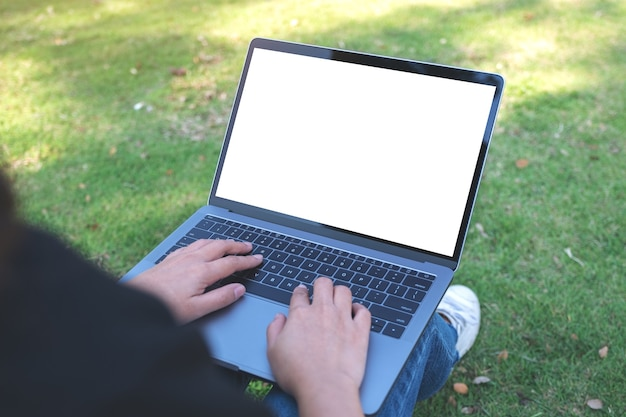 Makieta obraz kobiety za pomocą i wpisując na laptopie z pustym białym ekranem, siedząc na zewnątrz na tle przyrody