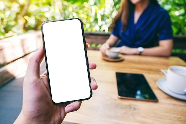 Makieta obraz mężczyzny trzymającego czarny telefon komórkowy z pustym białym ekranem z kobietą pijącą kawę w kawiarni
