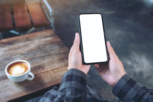 Makieta obraz przedstawiający ręce trzymając biały telefon komórkowy z pustym ekranem z filiżanką kawy na drewnianym stole w kawiarni