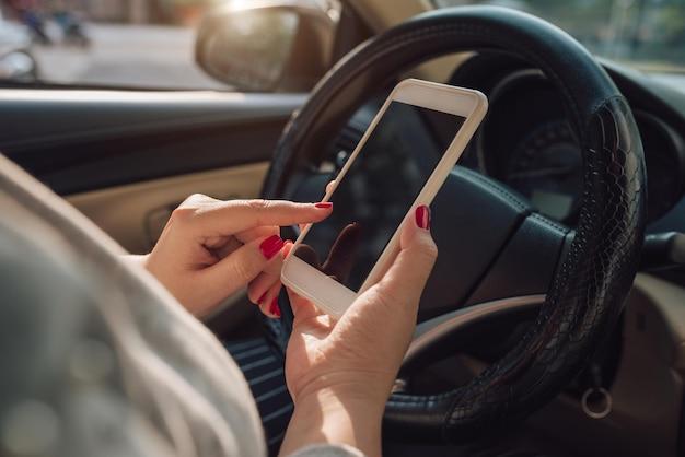 Makieta obraz ręki kobiety przy użyciu smartfona mobilnego z pustego ekranu podczas jazdy samochodem i wychodzenia z domu. ścieżka przycinająca.