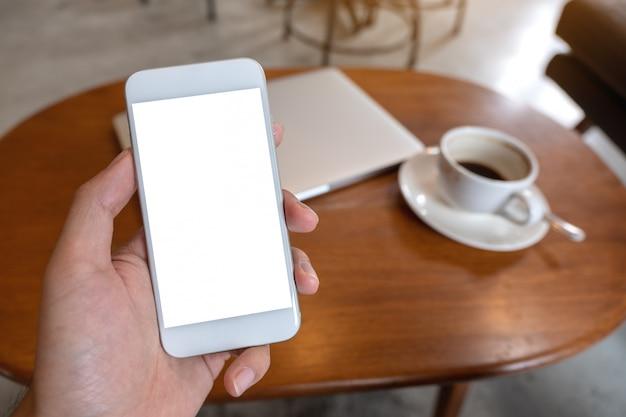 Makieta obraz ręki trzymającej biały telefon komórkowy z pustym ekranem pulpitu z filiżanką kawy i laptopa na stole