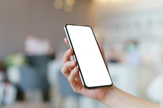 Makieta obraz ręki trzymającej telefon komórkowy z pustym białym ekranem.