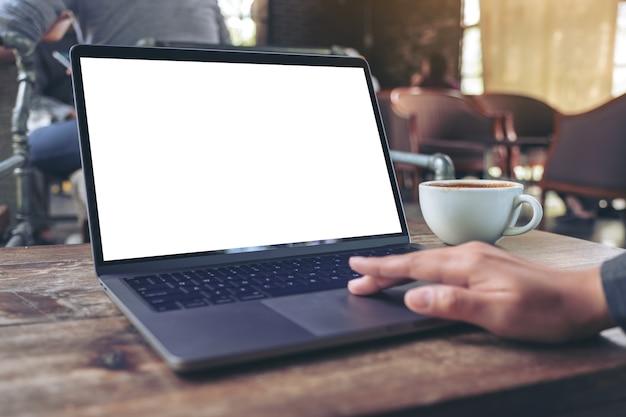 Makieta obrazu dłoni za pomocą płytki dotykowej laptopa i dotykania jej z pustym białym ekranem pulpitu