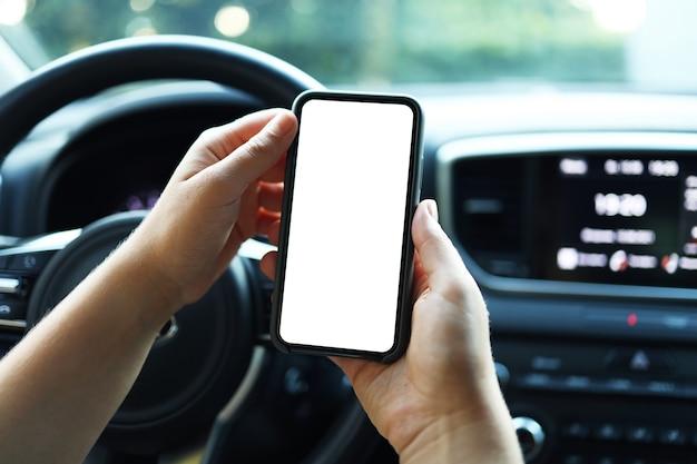 Makieta obrazu, dziewczyna używająca pustego białego ekranu smartfona w samochodzie w słoneczny dzień, dotykając ekranu lub wysyłając sms-y, skopiuj miejsce na reklamę