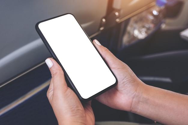 Makieta obrazu kobiecej ręki trzymającej czarny inteligentny telefon z pustym ekranem pulpitu w kabinie