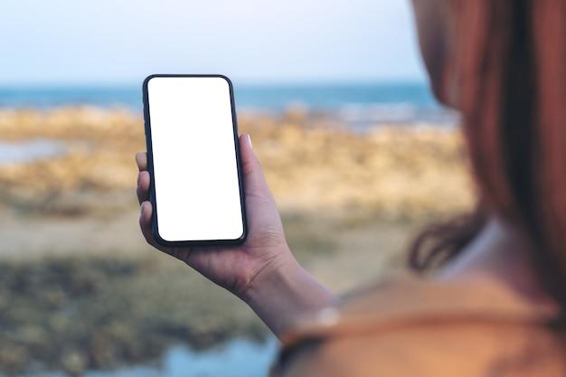 Makieta obrazu kobiecej ręki trzymającej czarny telefon komórkowy z pustym ekranem pulpitu przy plaży i morzu na tle błękitnego nieba
