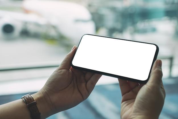Makieta obrazu kobiecej ręki trzymającej i używającej czarnego telefonu komórkowego z pustym ekranem podczas siedzenia na lotnisku